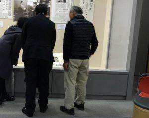 白井善吾(右)さんの案内で、「夜間中学生」展を見学する前川喜平さん(中)