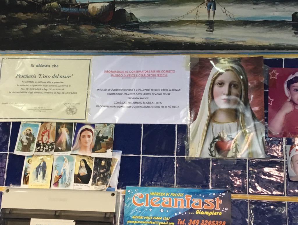 いつも行くお魚屋さん。壁にマリア様や聖人のブロマイド的なものが店の営業許可証や自分の子供の写真と一緒にペタペタ貼ってあります